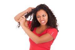 Giovane donna afroamericana che pettina capelli Immagini Stock