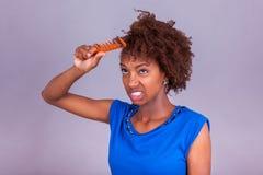 Giovane donna afroamericana che pettina i suoi capelli crespi di afro - Blac Fotografie Stock Libere da Diritti