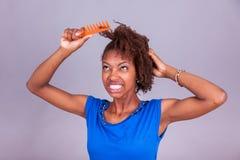 Giovane donna afroamericana che pettina i suoi capelli crespi di afro - Blac immagine stock libera da diritti