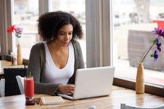 Giovane donna afroamericana che si siede al caffè con il computer portatile Immagini Stock Libere da Diritti