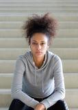 Giovane donna afroamericana che si siede sui punti con le cuffie Fotografia Stock