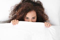 Giovane donna afroamericana che si trova sotto la coperta bedtime immagini stock