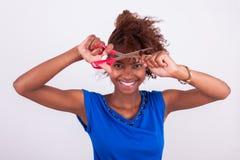 Giovane donna afroamericana che taglia i suoi capelli crespi di afro con la s immagini stock libere da diritti