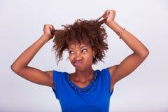 Giovane donna afroamericana che tiene i suoi capelli crespi di afro - Blac fotografie stock libere da diritti