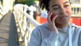 Giovane donna afroamericana dell'adolescente della ragazza della corsa mista che per mezzo del telefono cellulare archivi video