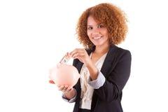 Giovane donna afroamericana di affari che tiene un porcellino salvadanaio - Afr Fotografie Stock