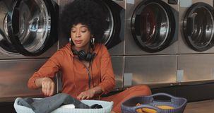 Giovane donna afroamericana felice che ordina la merce nel carrello della lavanderia che ordina i vestiti prima del lavare seduta video d archivio