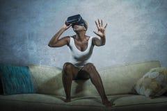 Giovane donna afroamericana nera curiosa attraente che indossa gli occhiali di protezione di visione di VR 3d che godono dell'esp Fotografie Stock