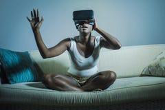Giovane donna afroamericana nera curiosa attraente che indossa gli occhiali di protezione di visione di VR 3d che godono dell'esp Fotografie Stock Libere da Diritti