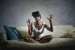 Giovane donna afroamericana nera curiosa attraente che indossa gli occhiali di protezione di visione di VR 3d che godono dell'esp Immagini Stock