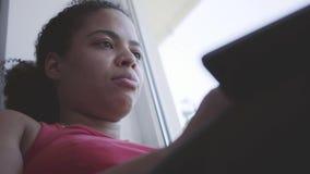 Giovane donna afroamericana sveglia che si siede sul davanzale della finestra che scrive sul suo computer portatile Ragazza felic stock footage