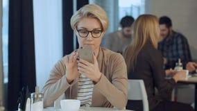 Giovane donna al caffè del caffè ed al telefono cellulare beventi usando Immagini Stock