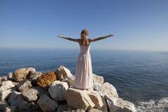 Giovane donna al mare che sta sulla roccia Fotografie Stock Libere da Diritti