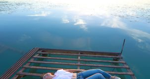 Giovane donna al pilastro dal fiume al tramonto stock footage