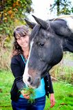 Giovane donna all'aperto alimentando un cavallo immagini stock