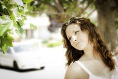 Giovane donna all'aperto che esamina un albero Immagini Stock Libere da Diritti