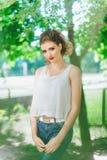 Giovane donna all'aperto in maglietta bianca e jeans, con trucco luminoso, labbra rosse Esaminando la macchina fotografica Fotografia Stock