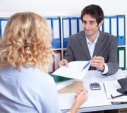 Giovane donna all'ufficio che firma un contratto Immagini Stock