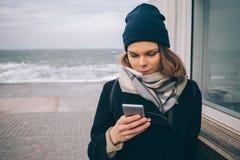 Giovane donna alla moda in cappotto, cappello del beanie e sciarpa fotografie stock