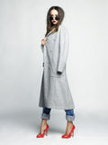 Giovane donna alla moda in cappotto grigio di grande misura fotografia stock libera da diritti