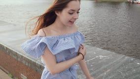 Giovane donna alla moda che cammina sul lungomare nella città stock footage
