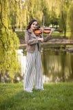 Giovane donna alla moda che gioca il violino nel parco Il piano generale immagine stock