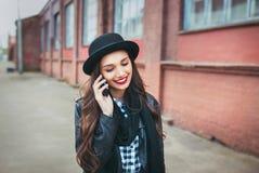Giovane donna alla moda che parla sul telefono in una via della città Fotografia Stock
