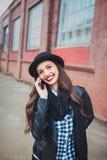 Giovane donna alla moda che parla sul telefono in una via della città Fotografia Stock Libera da Diritti