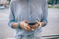 Giovane donna alla moda che porta camicia blu facendo uso dello Smart Phone fotografia stock libera da diritti
