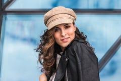 Giovane donna alla moda che posa contro le finestre di vetro all'aperto immagini stock libere da diritti