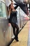 Giovane donna alla moda che posa vicino al treno al sottopassaggio di NYC Immagine Stock Libera da Diritti