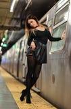 Giovane donna alla moda che posa vicino al treno al sottopassaggio di NYC Immagini Stock