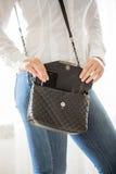 Giovane donna alla moda che prende cellulare dalla borsa Fotografia Stock