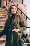 Giovane donna alla moda che sta posante su una vecchia scala di legno fotografie stock
