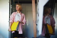 Giovane donna alla moda che tiene libro giallo luminoso che sta scaffale vicino nell'interno domestico Fotografie Stock Libere da Diritti