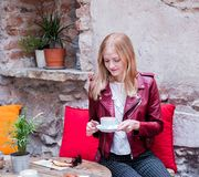 Giovane donna alla moda con i oudoors di seduta del croissant e del caffè al terrazzo del caffè fotografia stock libera da diritti