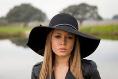 Giovane donna alla moda con il bello cappello nel campo Immagini Stock Libere da Diritti
