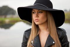 Giovane donna alla moda con il bello cappello nel campo Fotografia Stock Libera da Diritti