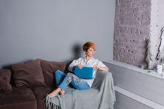 Giovane donna alla moda con il computer portatile in mani sul sofà ed esaminare macchina fotografica Vestito in camicia bianca e  Immagini Stock Libere da Diritti