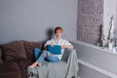 Giovane donna alla moda con il computer portatile in mani sul sofà ed esaminare macchina fotografica Vestito in camicia bianca e  Fotografie Stock