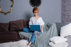 Giovane donna alla moda con il computer portatile in mani sul sofà ed esaminare computer portatile Vestito in camicia bianca e je Fotografia Stock Libera da Diritti