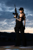 Giovane donna alla moda con la pistola fotografia stock libera da diritti