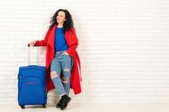 Giovane donna alla moda con la valigia blu che sta vicino al muro di mattoni vuoto bianco fotografia stock