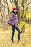 Giovane donna alla moda con una grande borsa nel parco di autunno Fotografia Stock