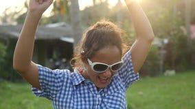 Giovane donna alla moda felice in occhiali da sole che ballano al sole fra le palme tropicali che gode della sua vacanza al tramo archivi video