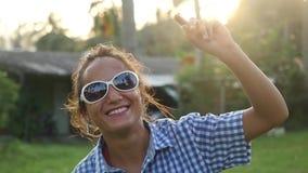 Giovane donna alla moda felice in occhiali da sole che ballano al sole fra le palme tropicali che gode della sua vacanza al tramo video d archivio