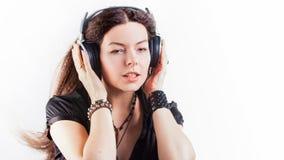 Giovane donna alla moda in grandi cuffie che ascolta la musica e divertiresi immagine stock libera da diritti
