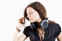 Giovane donna alla moda in grandi cuffie che ascolta la musica e divertiresi immagine stock