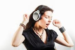 Giovane donna alla moda in grandi cuffie che ascolta la musica e divertiresi immagini stock libere da diritti
