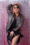 Giovane donna alla moda incantante in occhiali da sole vicino a lamé fotografia stock libera da diritti